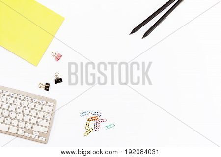 Computer Keyboard, A Yellow Pad, Two Black Pencil And Clips For Paper On White Background. Minimal C