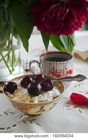 Cottage cheese with cherries in a plate with a teaspoon, against a background of tea and a burgundy peony. On the table with a white tablecloth