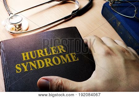 Hands holding book Hurler syndrome. Medical concept.