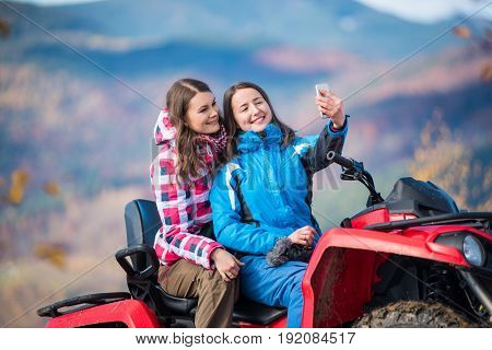 Close-up Two Happy Girls In Winter Jackets On Red Atv Smiling And Makes Selfie On The Phone With Blu