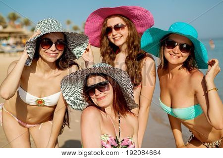 Four young beautiful girls in bathing suits and sunglasses on the seashore