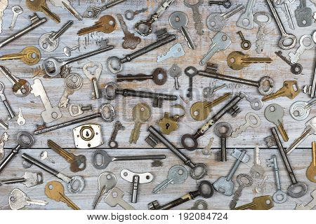 Overhead view of many different old keys in a mess on wooden background concept