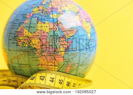 health in world concept measuring tape and globe on yellow background
