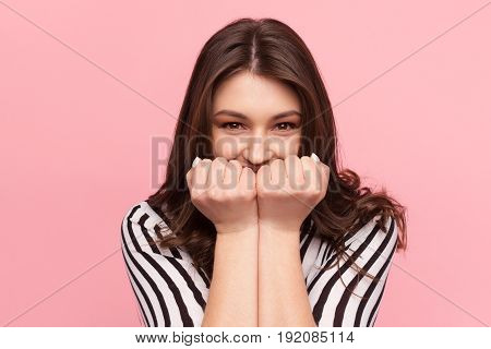 Excited woman looking at camera and holding fists up to mouth on the pink background.