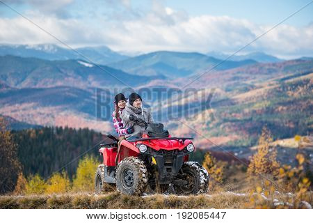 Happy Couple In Winter Sporty Clothing On Red Four-wheeler Atv In Mountains, Girl Sitting Behind Man