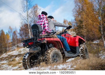 Woman Sitting Behind Man Hugging Him On Red Four-wheeler Atv At Snowy Hill In The Mountains . Beauti