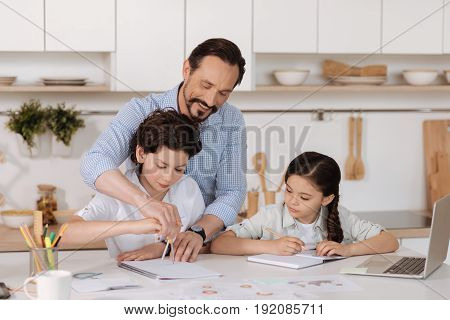 Help with love. Handsome young father helping his son to inscribe a circle with a compass by directing his hand while his daughter looking at it intently