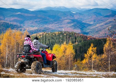 Rear View Of Couple In Winter Clothing Driving A Quad Bike Atv At The Hill On The Background Of Beau