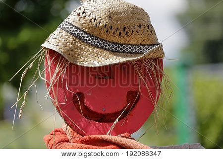A scarecrow in wood with a straw hat