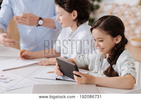 Entertainment time. Cute little girl distracting herself from doing home assignments by playing on her tablet while her father and son doing sums in the background