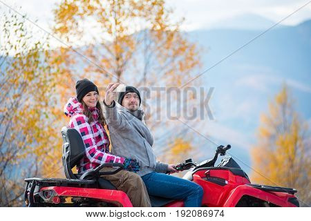 Close-up Of Man With Woman In Winter Clothing On Red Quad Bike Makes Selfie On The Phone Against Blu