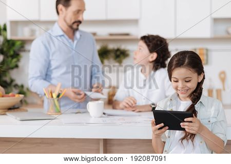 Having fun. The focus being on the cheerful petite girl watching a video on the tablet while her father and brother discussing something in the background