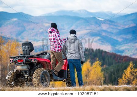 Rear View Of Woman Standing On A Red Quad Bike And Keeps The Shoulder Standing Next Man Enjoying The