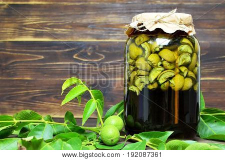 Preparing liqueur made of green walnuts on wooden background