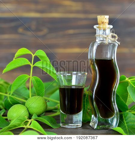 Close up of green walnut liqueur on wooden background