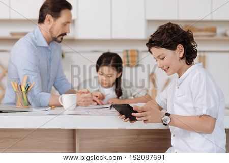 Hilarious video. Charming wavy-haired boy sitting at the kitchen counter and watching a funny video on his tablet while his father and sister doing sums