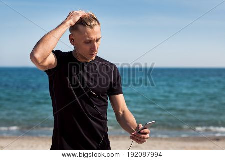 Young man wearing sportswear and holding smartphone with headphones on background of sea.