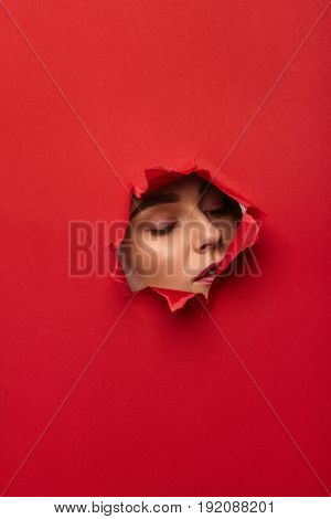 Female face in hole torn in red paper.