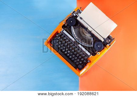 Workspace with orange vintage retro typewriter on blue and orange background