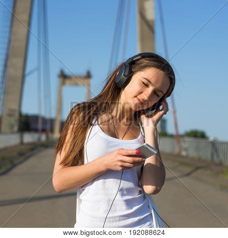 Teenage woman walking in old bridge. Summer hot weather at city.