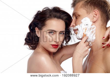 Side view of nude woman with red lips looking at camera while shaving handsome man.
