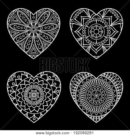 Doodle hearts set. Outline floral design elements in a heart shape. Coloring book pattern. Decorative hearts on black. Love, acceptance, positive energy concept. Vector illustration.
