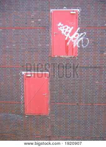 Two Red Doors In Brick Wall Without Any Platform Or Stairs