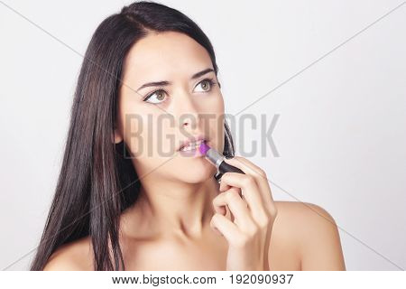 Closeup Of Young Caucasian Woman Applying Lipstick