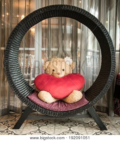 Bear doll with red heart pillow under black share