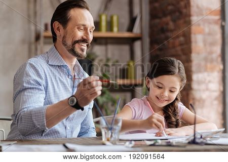 Inspiring co-creation. Joyful young father holding a brush, being ready to apply some strokes on the picture thus helping his cute little daughter to finish up a picture