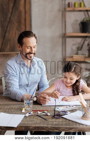 Creating together. Charming young father and his petite pleasant daughter sitting at the table and painting a picture with watercolors, being happy to do it together