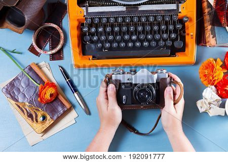 Workspace with someone hands holding old photo camera, on table with orange vintage typewriter