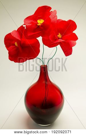 closeup of red origami flowers with vase