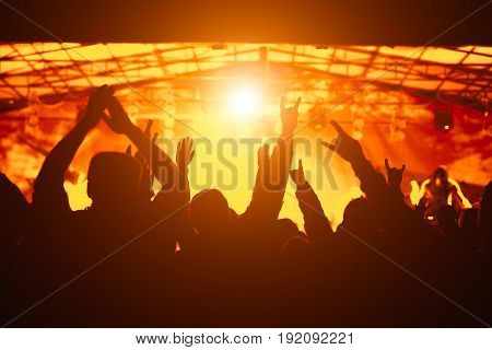 Silhouette of hands, cheering crowd at concert