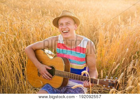 A man is playing guitar in the field at relax day with sun light