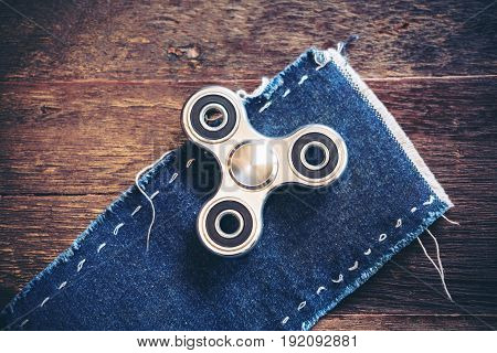 Top view image of a metal silver color fidget spinner on jean cloth with wooden table background