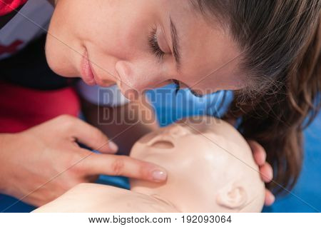Infant Resuscitation On Cpr Dummy By Young Woman, Color Image