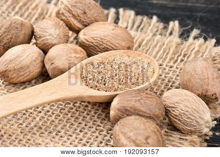 Nutmeg powder in a spoon with scattered nuts on the burlap and table