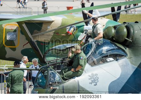 BERLIN GERMANY - JUNE 03 2016:Technicians inspect attack helicopter with transport capabilities Mil Mi-24 Hind. Czech Air Force. Exhibition ILA Berlin Air Show 2016
