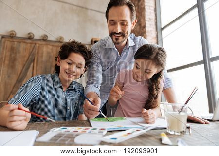 Making life colorful. Pleasant cheerful family looking happy while bonding to each other and creating a beautiful watercolor painting together.