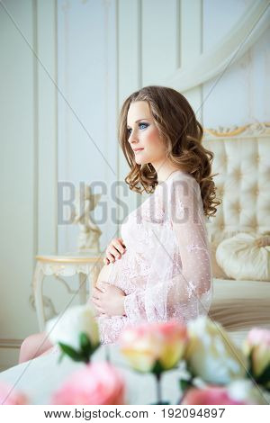 pregnancy, rest, people and expectation concept - happy pregnant woman sitting on bed and touching her belly at home