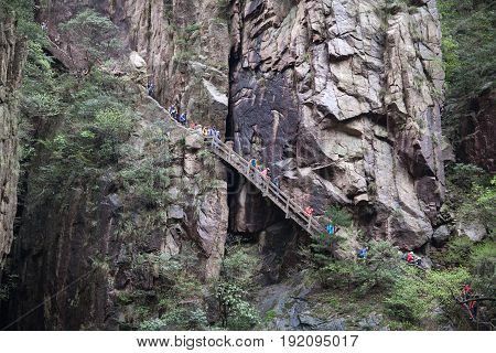HUANGSHAN, CHINA - APRIL 23, 2014: Tourists walking in forest in Huangshan National Park (Yellow Mountains) in Anhui Province.