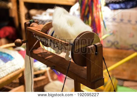 flyer and bobbin of a wooden spinning wheel with hand-spun natural wool on an outdoor craft market