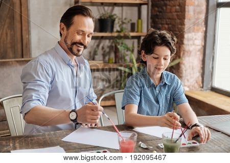 Starting from scratch. Handsome bearded father and his charming son sitting at the table in the living room and enjoying themselves while starting to paint new pictures