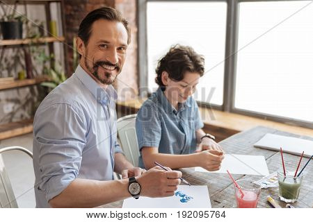 Sincerely happy. Charming young father painting a watercolor picture together with his son while looking pleased to spend some time with him