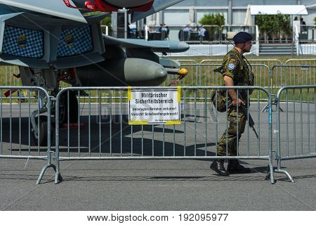 BERLIN GERMANY - JUNE 03 2016: A soldier guards the Eurofighter Typhoon aircraft. German Air Force. Exhibition ILA Berlin Air Show 2016