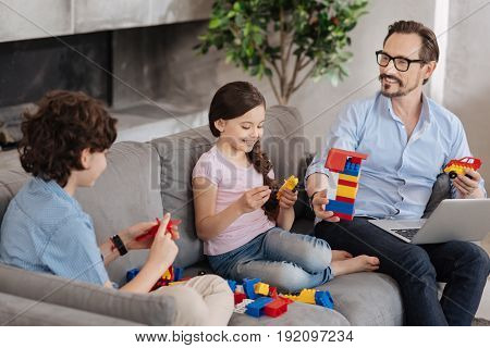 Enjoyable game. Lovely single-parent family sitting on the sofa and assembling a colorful erector set, seemingly having a great time together