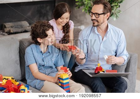 There you go. Petite little girl sitting on the sofa between her father and brother and taking a piece of an erector set from her fathers hands while her brother building a tower