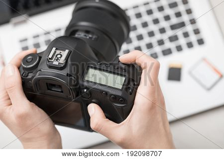Modern digital DSLR camera and computer workstation. Photography and videography concept.