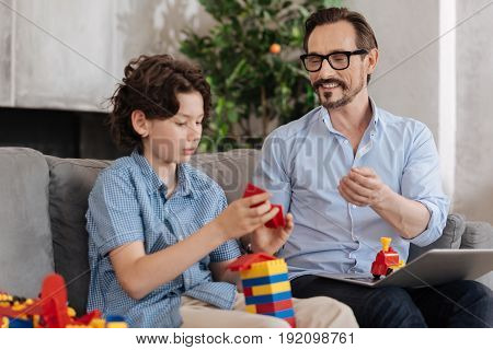Maximum concentration. Cute serious boy sitting on the sofa and being engaged into assembling erector set into a tower while his father addressing him with a smile